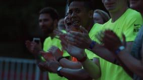 Os atletas multiculturais agrupam o aplauso cheering no estádio do ar livre filme