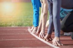Os atletas na sprint começam a linha no atletismo imagens de stock royalty free