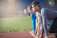 Os atletas na sprint começam a linha no atletismo imagem de stock royalty free