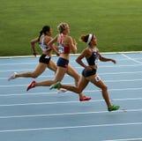 Os atletas no revestimento de 400 medidores competem Fotografia de Stock Royalty Free