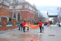 Os atores da rua guardam uma tela alaranjada e cumprimentam visitantes da celebração de Shrovetide em Moscou fotografia de stock royalty free