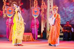Os atores não identificados aparecem em uma exibição do público da entrada gratuita da ópera chinesa em uma rua no ícone Sião foto de stock