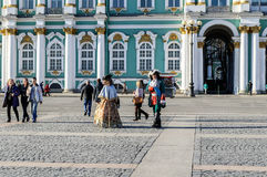 Os atores nas imagens de caminhadas de Peter The Great e da senhora de corte entre os turistas no palácio esquadram no fundo do H Imagem de Stock
