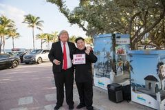 Os atores que jogam o trunfo e o Kim Jong-Un guardam o cartaz falsificado do ` da notícia do ` Praia de Fort Lauderdale foto de stock