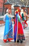Os atores vestiram-se em trajes nacionais coloridos cumprimentam povos na rua Imagem de Stock