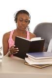 Os auscultadores cor-de-rosa do tanque da mulher leram um livro Fotos de Stock