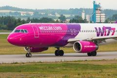 Os aviões alinham Wizzair que taxiing na pista de decolagem do aeroporto Foto de Stock