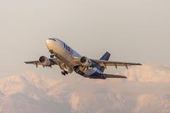 Os aviões da carga de Fedex Federal Express Airbus A310 que descolam na frente da neve tamparam montanhas Fotografia de Stock Royalty Free