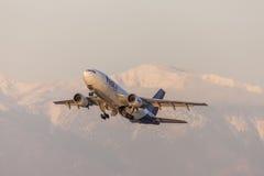 Os aviões da carga de Fedex Federal Express Airbus A310 que descolam na frente da neve tamparam montanhas Fotos de Stock Royalty Free