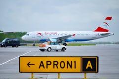 Os aviões de Austrian Airlines Airbus A320 e seguem-me carro na pista de decolagem do aeroporto internacional de Pulkovo em St Pe Imagens de Stock