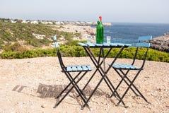 Os azuis celestes apresentam e cadeiras em um ponto panorâmico de Menorca Imagens de Stock