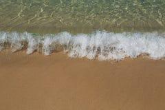 Os azuis celestes molham e amarelam a areia, onda do close-up fotos de stock