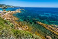 Os azuis celestes molham na praia rochosa em Menerbes Fotos de Stock Royalty Free