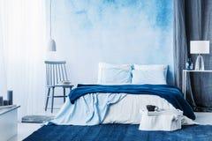 Os azuis marinhos atapetam no interior mínimo do quarto com a cobertura na cama imagens de stock royalty free
