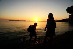 Os Backpackers mostram em silhueta na água Fotos de Stock