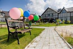 Os balões coloridos aproximam o brench na aléia e nas casas Fotografia de Stock Royalty Free