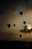 Os balões de ar quente decolam no céu da noite imagem de stock