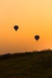Os balões mostram em silhueta com por do sol Imagem de Stock