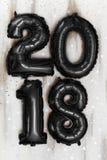 Os balões pretos metálicos brilhantes figuram 2018, Natal, balão do ano novo com as estrelas do brilho na tabela de madeira branc Imagem de Stock