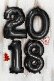 Os balões pretos metálicos brilhantes figuram 2018, Natal, balão do ano novo com as estrelas do brilho na tabela de madeira branc Foto de Stock Royalty Free