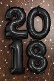 Os balões pretos metálicos brilhantes figuram 2018, Natal, balão do ano novo com as estrelas do brilho na tabela de madeira escur Fotos de Stock