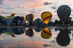 Os balões que inflam com uma reflexão no lago no Canberra Balloon festival o 13 de março de 2016 fotografia de stock