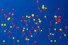 Os balões vermelhos e amarelos voam através do céu azul imagens de stock