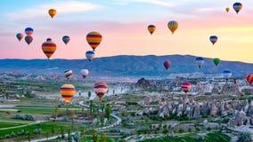 Os bal?es de ar quente coloridos que voam sobre a rocha ajardinam em Cappadocia Turquia fotos de stock royalty free