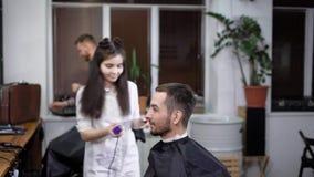 Os barbeiros fêmeas e masculinos estão trabalhando com os clientes com cabos do corte no barbeiro A jovem mulher está usando o ha filme