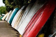 Os barcos coloridos inclinam-se contra a parede no lado de mar inglês do país com barcos e Mountain View foto de stock royalty free