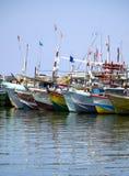Os barcos de Fisher na praia na manhã iluminam-se Foto de Stock