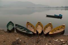 Os barcos de madeira verdes e amarelos na costa do lago Feva, a água calma do lago como um espelho refletem montanhas azuis no CC Imagem de Stock