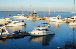 Os barcos de motor na doca refletem em águas da manhã foto de stock
