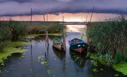 Os barcos de pesca amarraram na ponte de madeira pequena sobre o rio Fotos de Stock