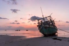 Os barcos de pesca arruinados de madeira velhos ajustaram-se encalhada na praia no tempo do por do sol foto de stock royalty free