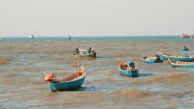 Os barcos de pesca pequenos navegam ao longo do mar luxúria em ondas Peixes da captura dos pescadores no mar filme