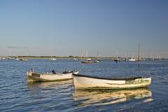 Os barcos de pesca velhos refletiram na água calma durante o por do sol do verão Fotografia de Stock Royalty Free