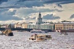 Os barcos de prazer navegam ao longo de Neva River contra da construção de Kunstkammer em St Petersburg Fotos de Stock Royalty Free