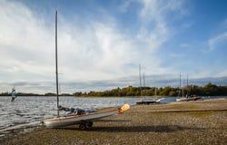 Os barcos de Sailng alinham na costa que prepara-se para lançar-se em um dia ensolarado do outono em Inglaterra, Reino Unido imagem de stock
