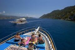 Os barcos do cruzeiro navegam após uma seção da cidade afundado na ilha de Kekova em Turquia Imagem de Stock Royalty Free
