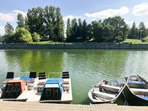 Os barcos e os catamarãs em um lago da lagoa em um canal do rio com água florescida verde são amarrados na costa foto de stock