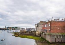 Os barcos e os navios amarraram em um porto pequeno, no coasta do fundo foto de stock royalty free