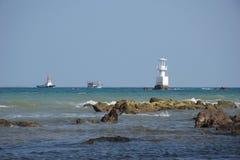 Os barcos e o farol na costa do oceano fotos de stock