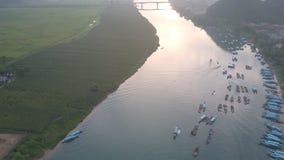 Os barcos flutuam na superfície larga calma do rio perto do banco no por do sol filme