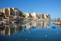 Os barcos malteses tradicionais refletiram na água azul do porto San Giljan fotografia de stock