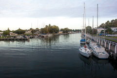 Os barcos na vila litoral abrigam com água calma Imagem de Stock