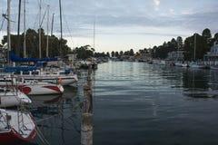 Os barcos na vila litoral abrigam com água calma Fotografia de Stock Royalty Free