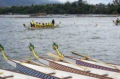 Os barcos nativos da cabeça do dragão da fileira dos esportes estacionados no lago suportam durante Dragon Cup Competition fotos de stock royalty free