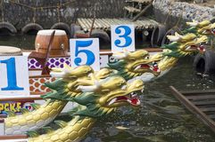 Os barcos nativos da cabeça do dragão da fileira dos esportes estacionados no lago suportam durante Dragon Cup Competition imagem de stock royalty free