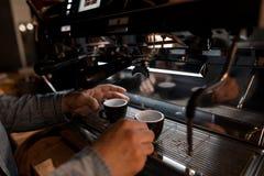 Os baristas masculinos das mãos guardam dois copos perto da máquina moderna do café A máquina profissional do café derrama a bebi imagem de stock royalty free
